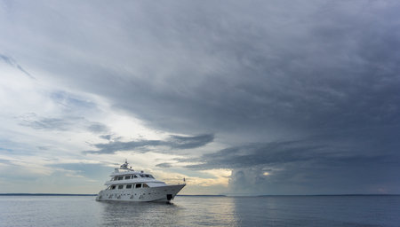 the entering: Boat entering storm with calm water Stock Photo