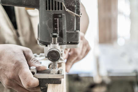 hinges: Blurred motion of carpenter working, preparing door for hinges Stock Photo