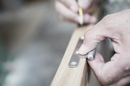 portones de madera: Primer plano de la mano con un l�piz de carpintero trabajando en bisagra de la puerta