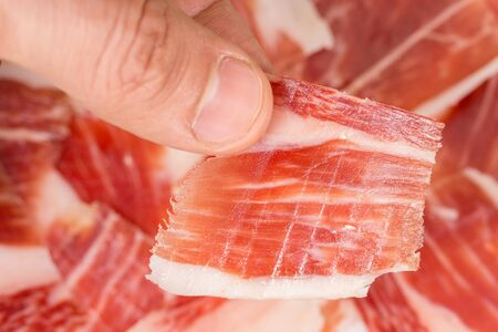 Top view of caucasian man hand taking Serrano ham slice photo