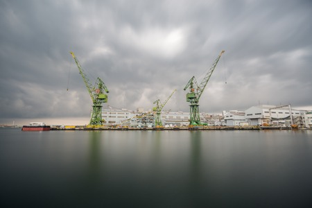 stormy clouds: Wide angle view of cranes on pier, stormy clouds, long exposure Stock Photo