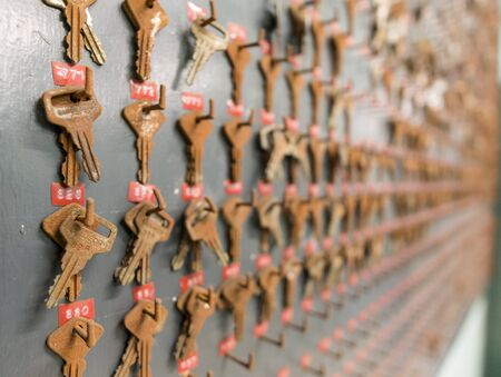 side keys: Side view of wall with rusty iron keys, shallow depth of field Stock Photo