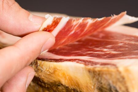 left hand: Caucasian man left hand over serrano ham with slice Stock Photo