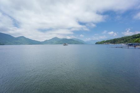 water s edge: Ampia vista del lago Chuzenji con barca turistica a Nikko, Giappone