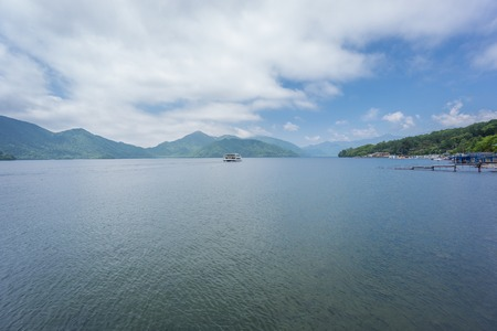 water s edge: Wide view of Lake Chuzenji with tourist boat in Nikko, Japan