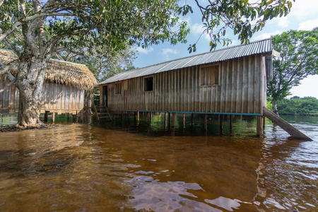 stilt house: Wide angle view of wooden house built in Amazon rainforest over black river, Brazil Stock Photo
