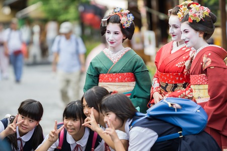 maiko: KYOTO, JAPAN - JUNE 10: Unidentified tourist women dress like a Maiko and take photo with children, Tourists usually makeup as Geishas (also known as Maiko) in Kyoto on June 10, 2015 in Japan