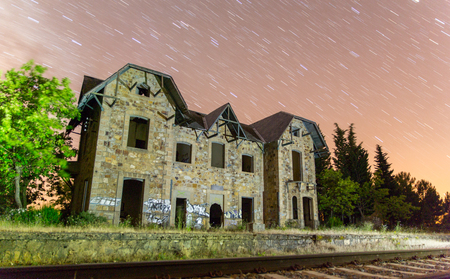 psyco: Night view of abandoned train station with star trails Stock Photo