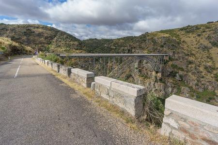 castile: Wide view of road to Requejo iron Bridge in Pino del Oro, Castile and Leon, Spain
