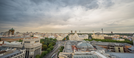 Ultra wide panoramic skyline of Madrid in a cloudy day, long exposure with car trails