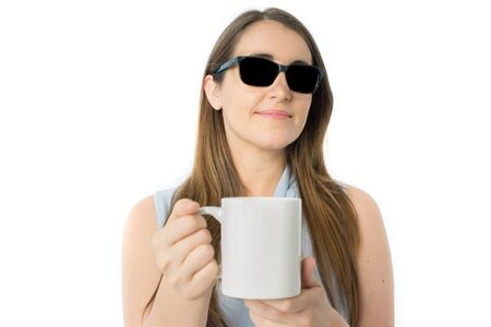 Front view of blind caucasian woman offering cup of coffee, focus in woman face, white cup of coffee for texts Stock Photo