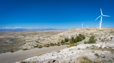 ''wide angle'': Wide angle view of windmills in plateau with mountain road