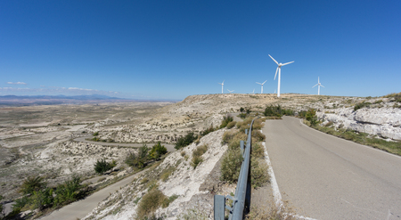 curve road: Wide angle view of windmills in plateau with mountain road and u-shape curve Stock Photo
