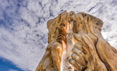 flee: Wide angle view of hands and trunk sculpture in Tordesillas against cloudy sky