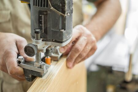 creating: Carpenter working over door edge, creating hinges holes, blurred motion Stock Photo