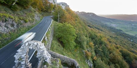 lonelyness: Blurred car driving up mountain road in autumn Stock Photo