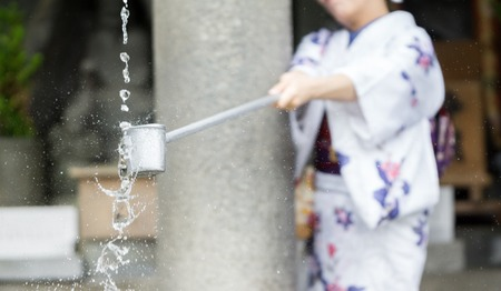 purification: Woman in traditional dressing takes water for purification at the entrance of Japanese temple Stock Photo