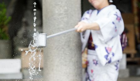 purification: Woman in traditional dressing takes water for purification at the entrance of Japanese temple #2