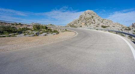 cornering: Mountain s-shape curved road to heaven, blue sky Stock Photo