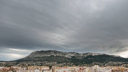 stormy clouds: Wide angle view of Montgo mountain over Denia roofs in Spain. Stormy clouds Stock Photo