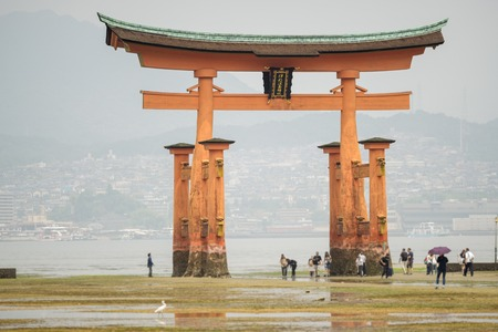 plan éloigné: Long shot of Miyajima with Floating Torii gate and blurred tourists, Japan. Banque d'images