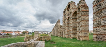 buttresses: Ultra wide panoramic view of Aqueduct of the Miracles in Merida against cloudy sky, Spain Stock Photo