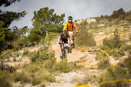 descends: VALENCIA - MARCH 6: Unidentified rider descends behind motorbike in international Chelva MTB-XCO competition in Chelva on march 6, 2016 in Valencia, Spain