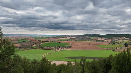 cultivated land: Cloudy sky and cultivated land with windmills in the skyline