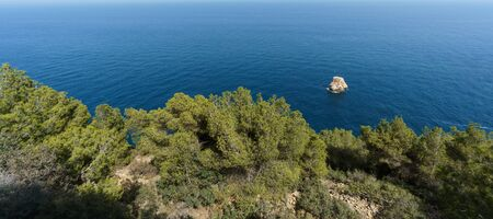 barrenness: Panoramic view of coastline with rock in the middle of the sea