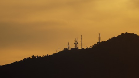plan éloigné: Long shot of sunset over mountains profile with communication towers, orange sky