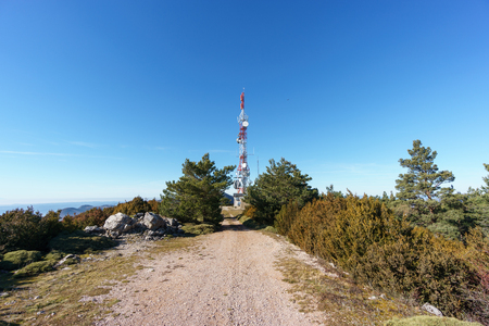 communication tower: Wide view of communication tower over blue sky on top of mountain