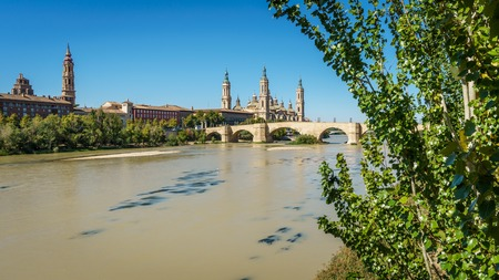 ebro: Panoramic view of El Pilar basilica and the Ebro River with tree. Long exposure, silk water