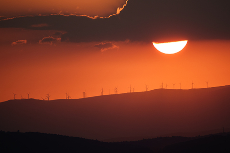 plan éloigné: Long shot of sunset over mountains profile with modern windmills, orange sky