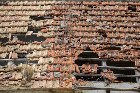 damaged roof: Detailed view of abandoned building with damaged tile roof Stock Photo