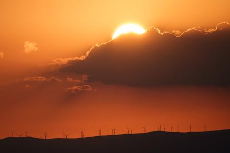 plan éloigné: Long shot of sunset over mountains profile with modern windmills, orange sky