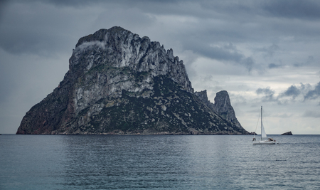 vedra: Picturesque and mysterious island of Es Vedra with sailing boat. Ibiza, Balearic Islands. Spain Stock Photo