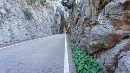 front end: wild driving over mountain road between big rock walls