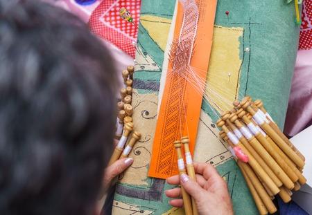 Elderly woman working on bobbin lace