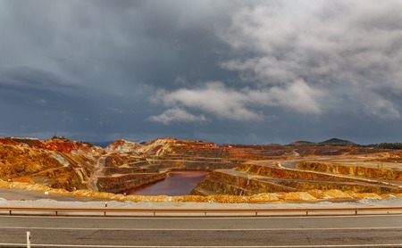 cooper: Wide angle view of copper mine open pit in Rio Tinto with road, cloudy day, Spain