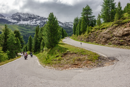 U-shape curved road in gavia pass with cyclists and motorbikes