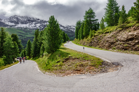 U-shape curved road in gavia pass with blurred cyclists