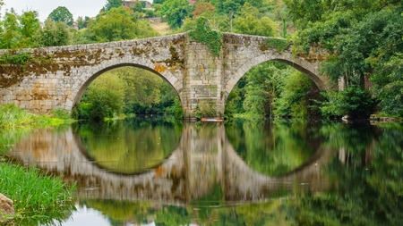 Reflection of river and medieval bridge in Allariz, Orense, Galicia, Spain