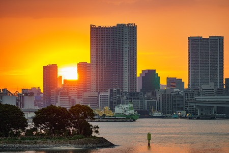 Sunset over office buildings in Tokyo with water reflection