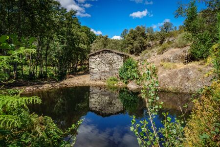 Old abandoned watermill and pond Stock Photo
