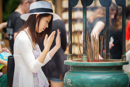 KYOTO, JAPAN- JUNE 7, 2015: Unidentified Japanese woman closes eyes and prays behind incense sticks in temple in Kyoto, Japan