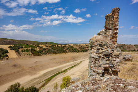 Ruins of castle and drought with dry dam