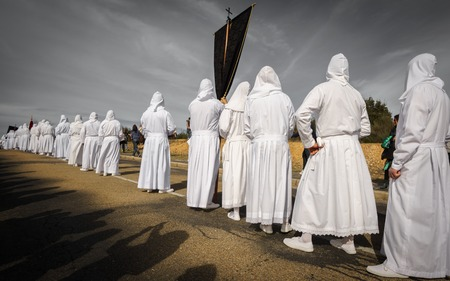 BERCIANOS, SPAIN- APRIL 3, 2015: Unidentified tourists enjoy the antique brotherhood procession with traditional clothes in Bercianos, Spain
