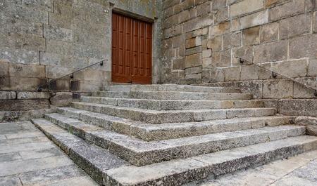 Stairs towards wooden door entrance Stock Photo