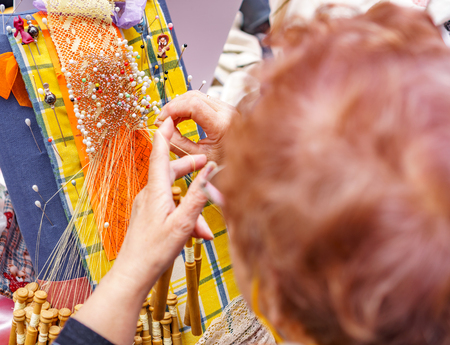Close-up of an elderly woman head working on bobbin lace Stock Photo