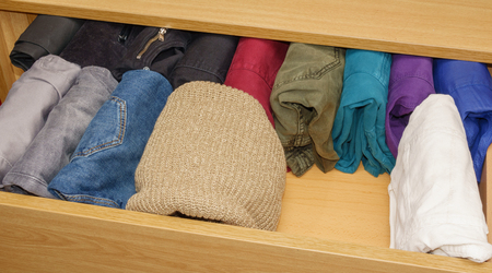 Open drawer with trouser and wool sweaters Stock Photo